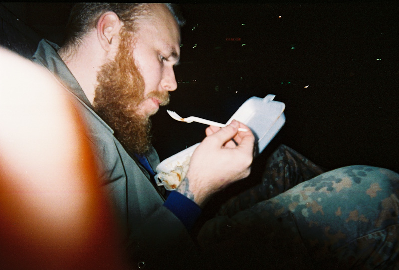 A bearded man eating from a styrofoam take away box with a plastic fork.