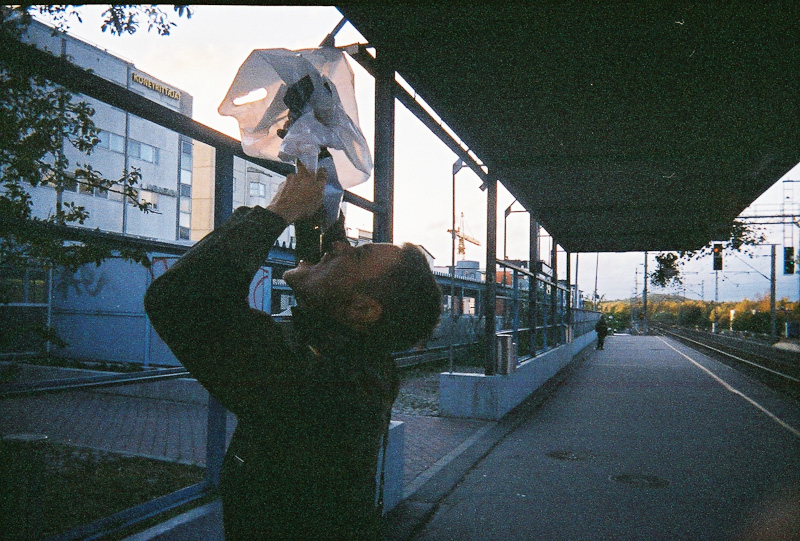 A man on a train stop holding a plastic bag above his head and liquid coming out into his mouth.