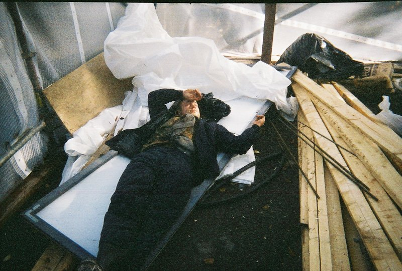 A man lying in a shed on a white board surrounded by construction materials such as two-by-fours.