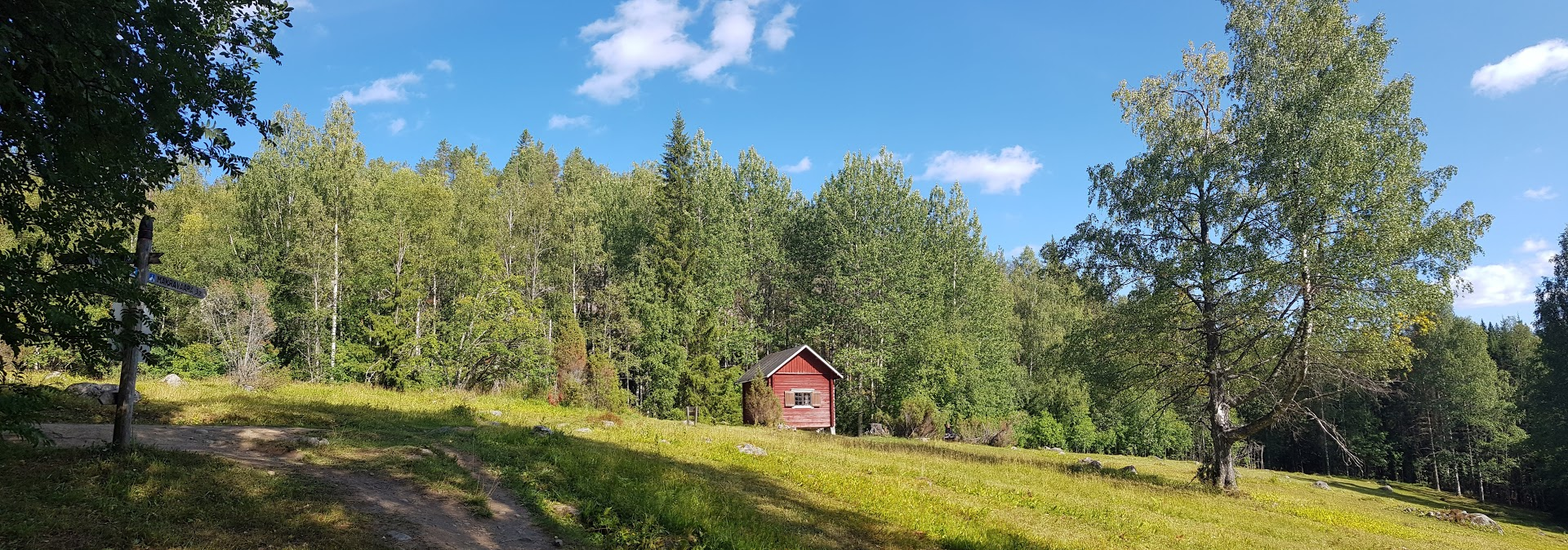 A grassland in the middle of a forrest with a small red building at the edge of the forest.