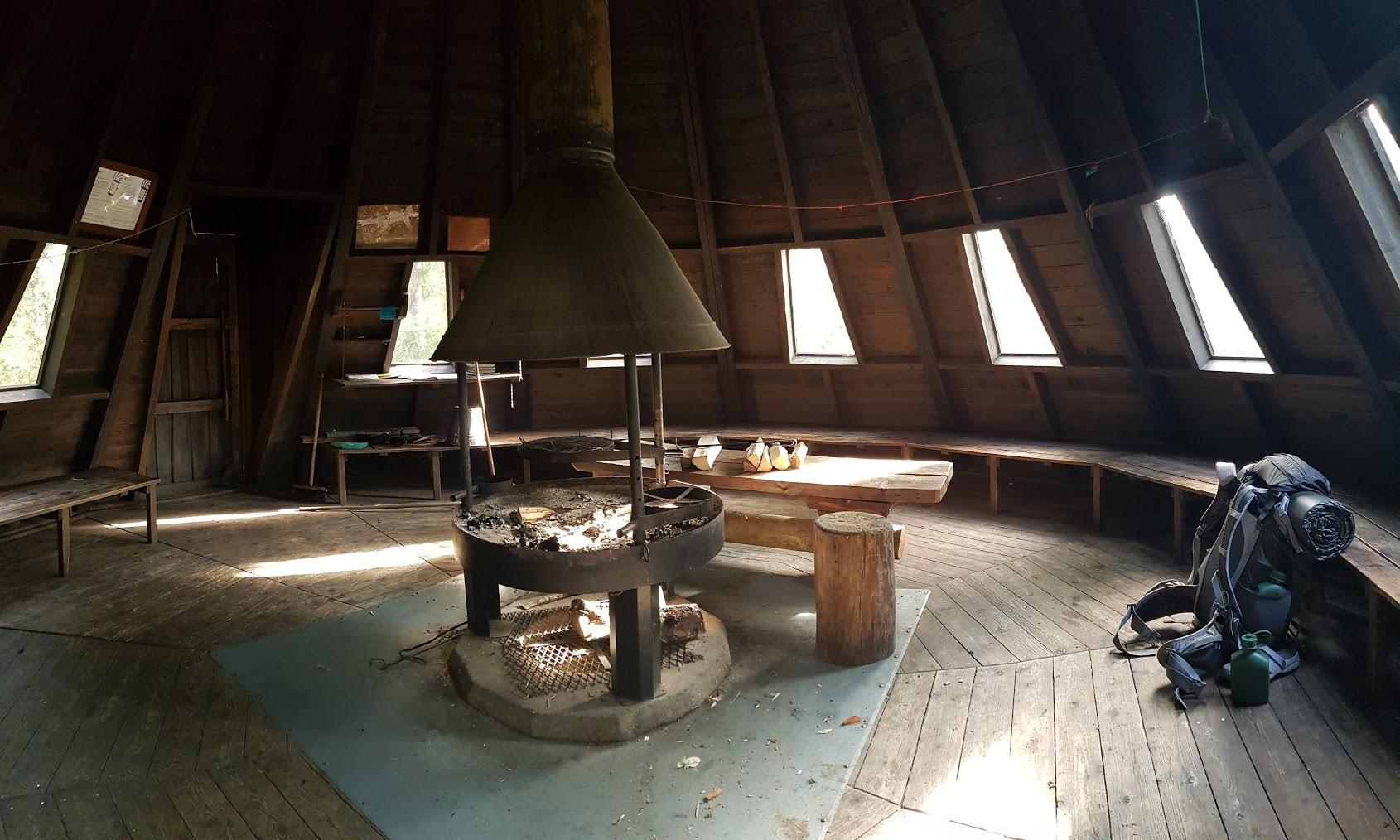 Inside a wooden teepee with a fireplace, a dining table and benches bordering the circular structure.