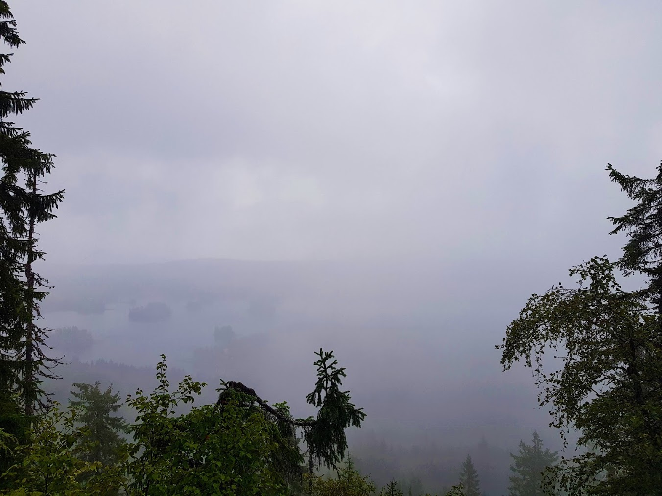 A foggy scenery from the hilltop towards a lake.