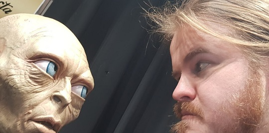 A man and Gollum staring each other in the eye.