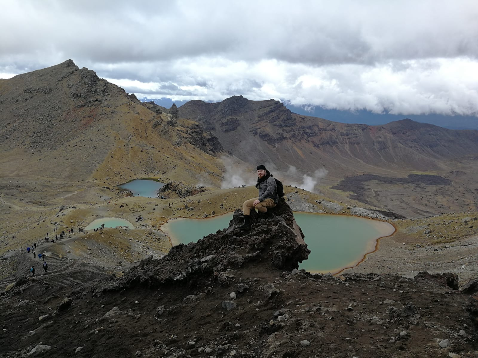 A man sitting on top of a hill with mountains and emerald mountain lakes on the background.