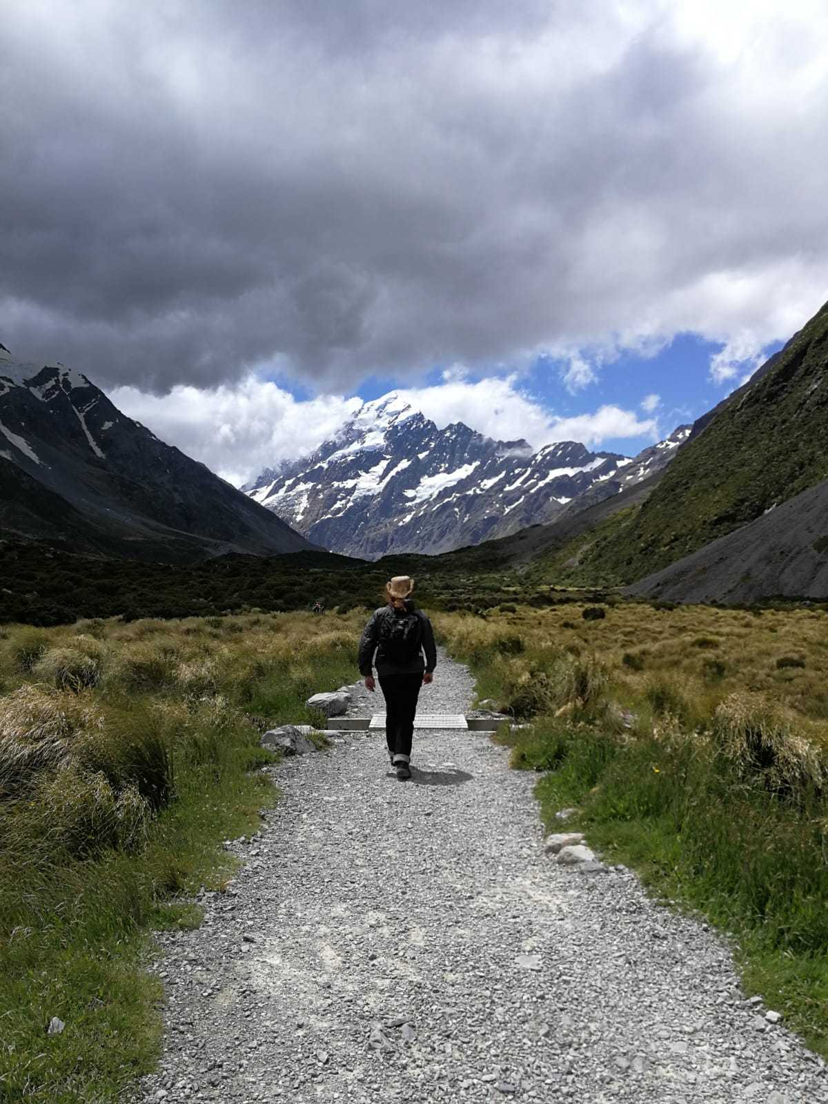 A man walking away from the camera along a stony path. In the distance some partially snow covered mountains and grass land.