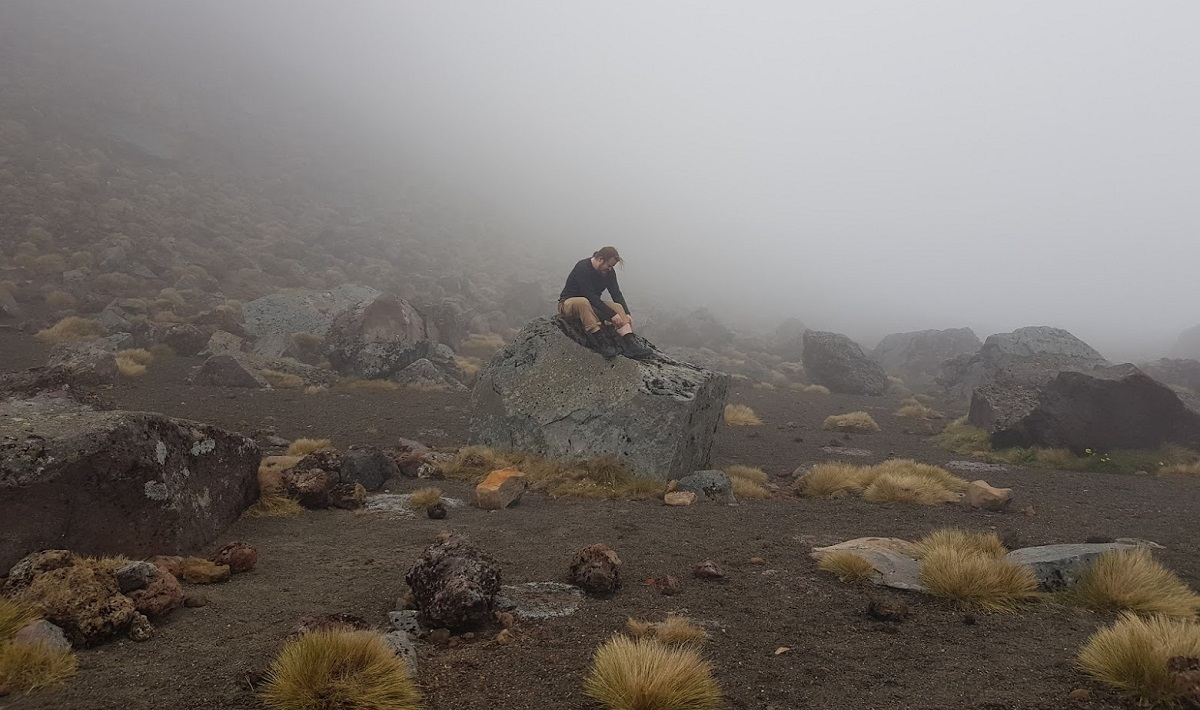 A foggy rock land with a man sitting on a large rock.