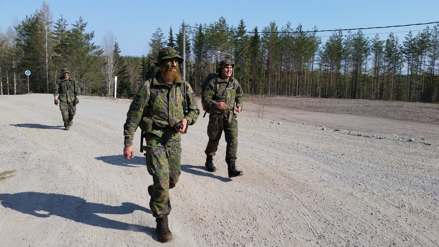 Three people walking on a dirt road in camouflage clothing.