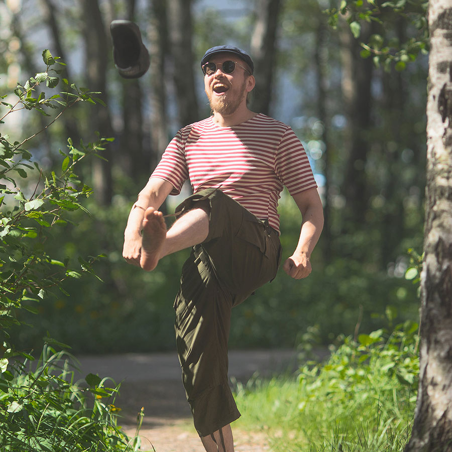 A man outdoors in the summer with a open mouth smile on his face having kicked his shoe on air.