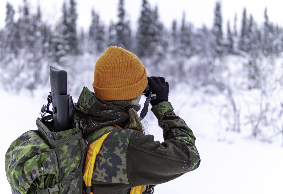 A hunter in the woods looking out with binoculars.