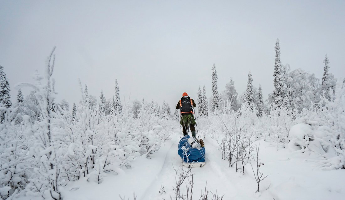 A hunter skiing through a snow filled scenery with oulling a sledge behind him.