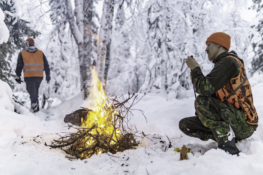 A hunter at a campfire in the woods.
