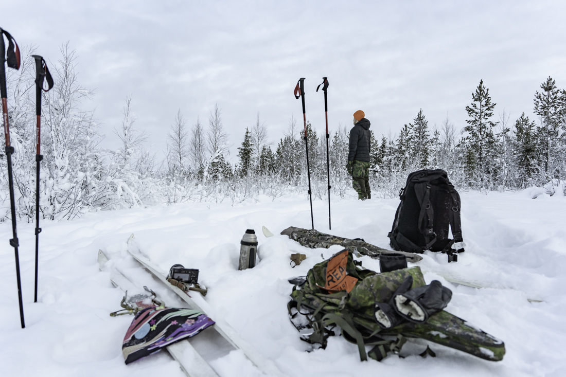 A break in the snowy woods with gear off and a hunter peerin at the distance.