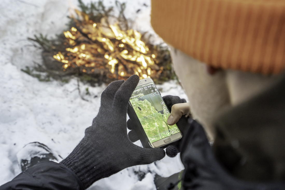 A hunter checking the map on a mobile phone next to a camp fire.