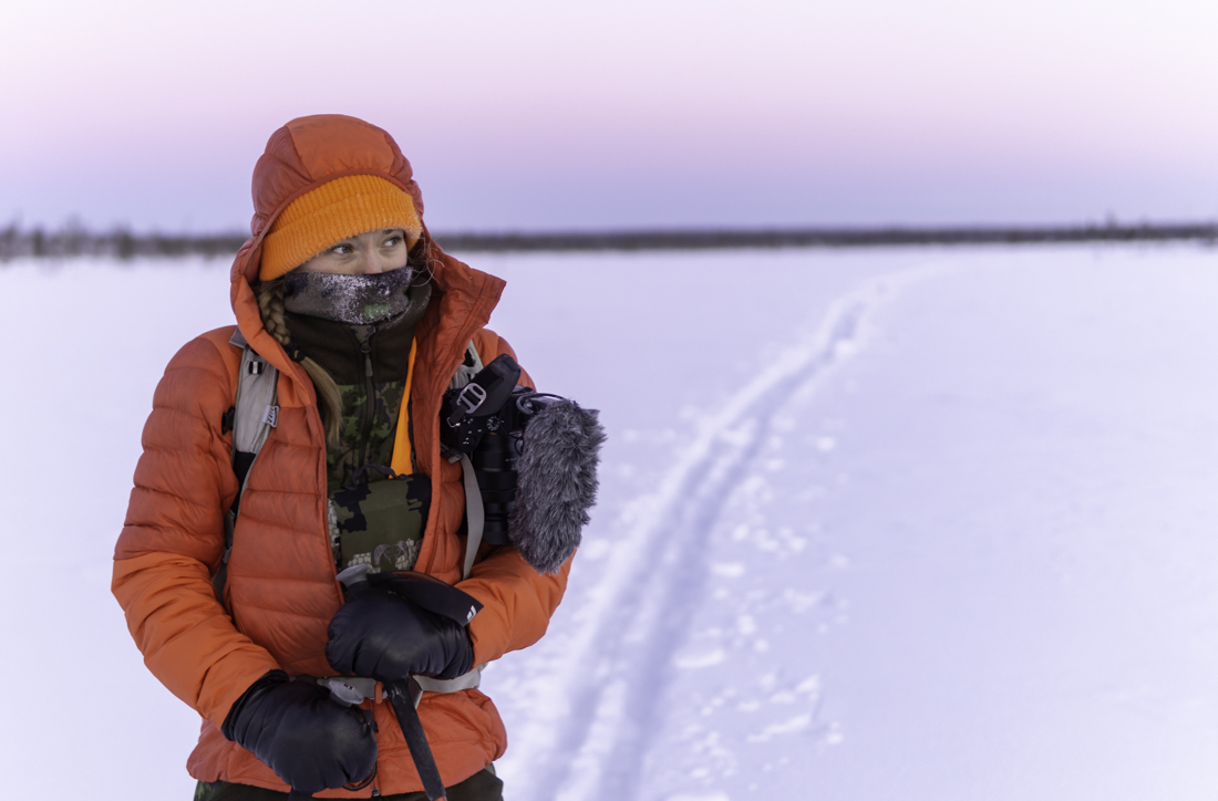 A hunter on a ski track at dawn with a puffer jacket on and a frosty scarf covering her face.