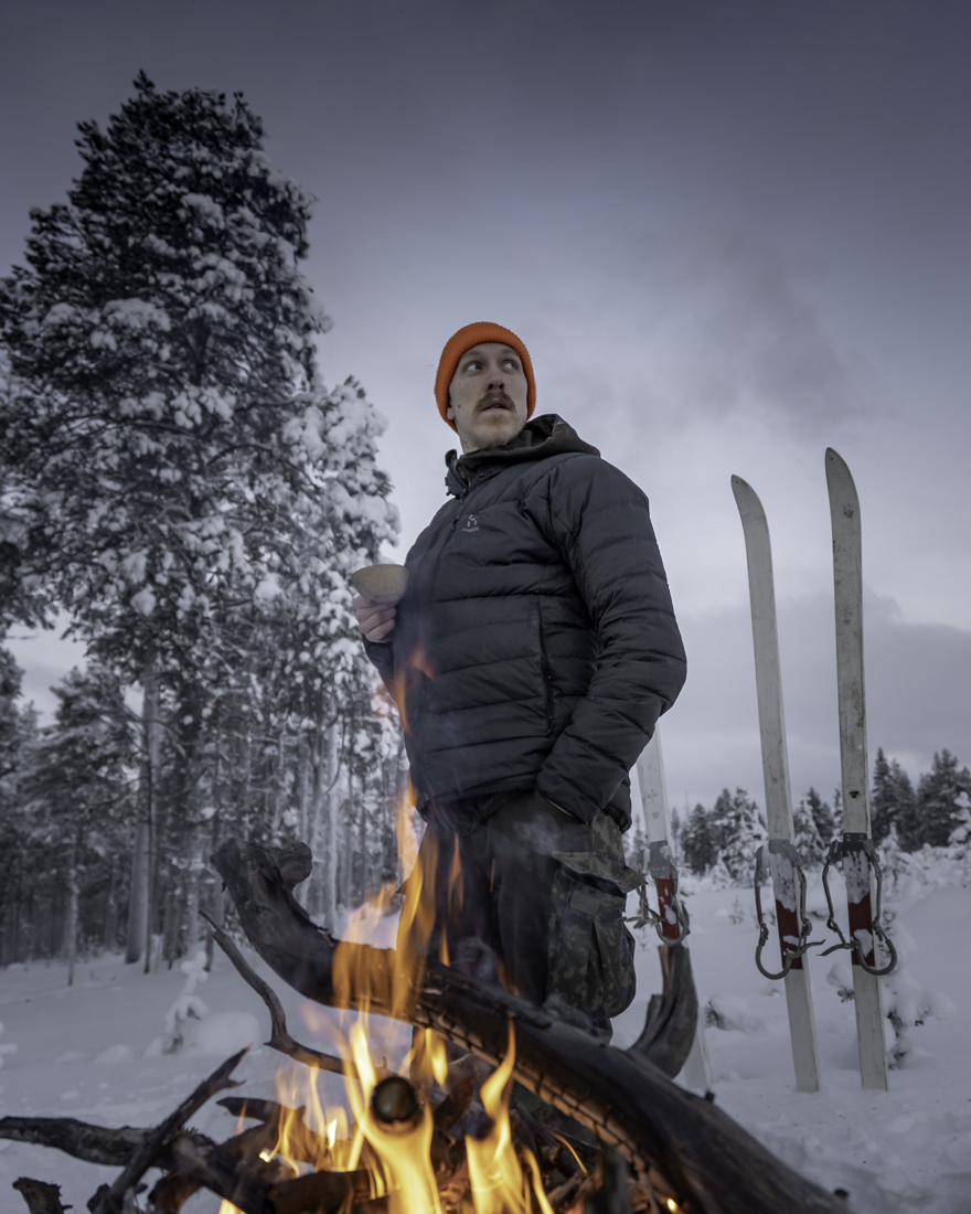 A skier at a campfire in the woods.