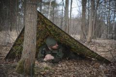 Särmä TST Rain poncho, M05 woodland camo. The poncho can be used to construct different types of emergency shelters.