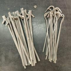 French F1 / F2 2-Person Tent, Surplus. The stakes may be either type: the stronger ones on the left or the lighter ones on the right, which weigh 25 grams (0.88 oz) a piece.