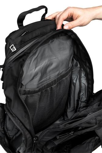 CamelBak Urban Assault Pack, black, with water bottle, surplus. The main compartment with a mesh pocket on one side and a closed pocket on the other.